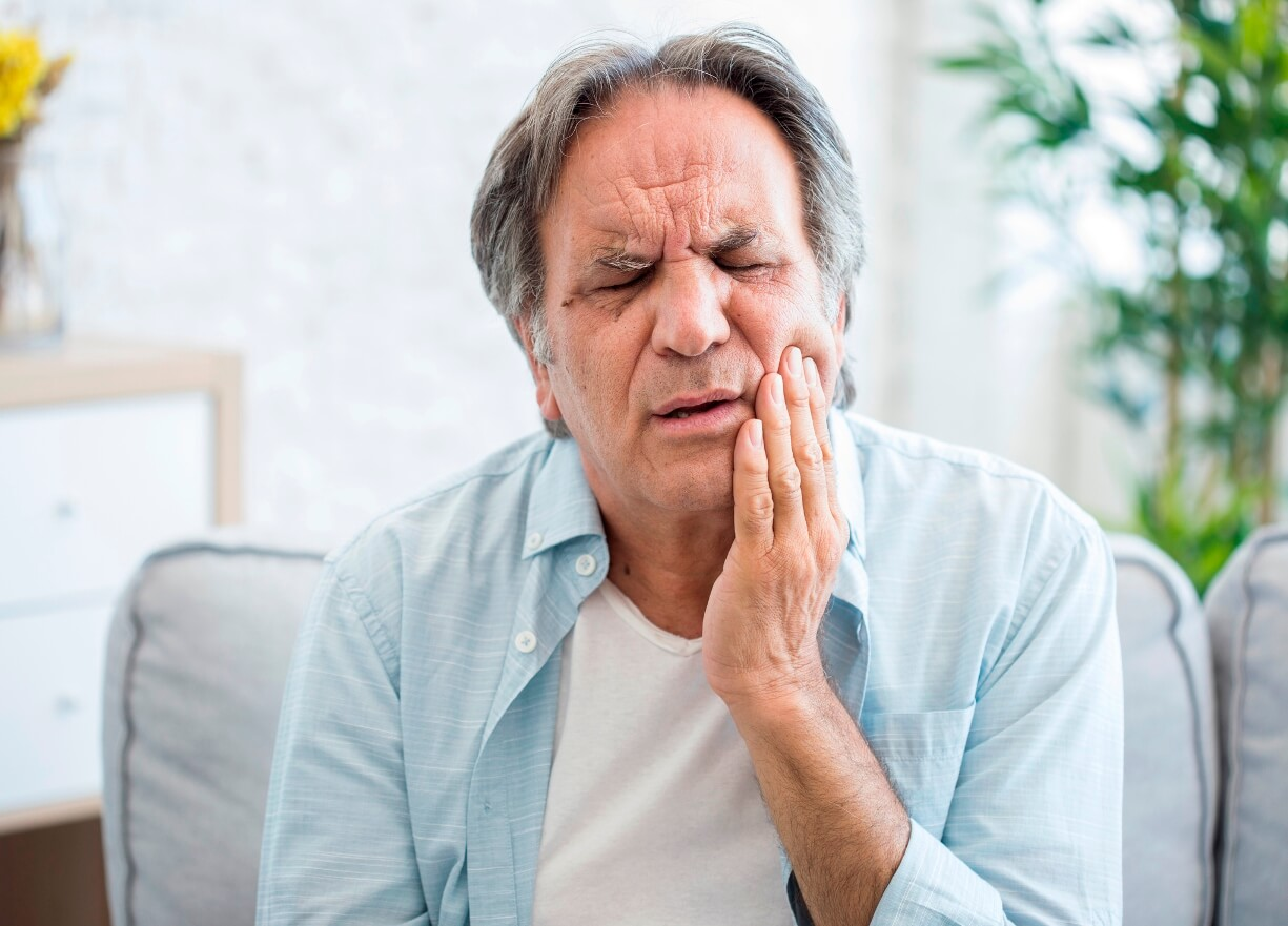 Senior man suffering from toothache symptoms
